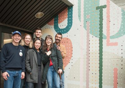 Paul Dangerfield with IDEA students in front of mural.